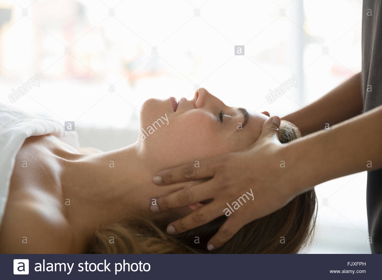 Serene woman with eyes closed receiving head massage - Stock Image