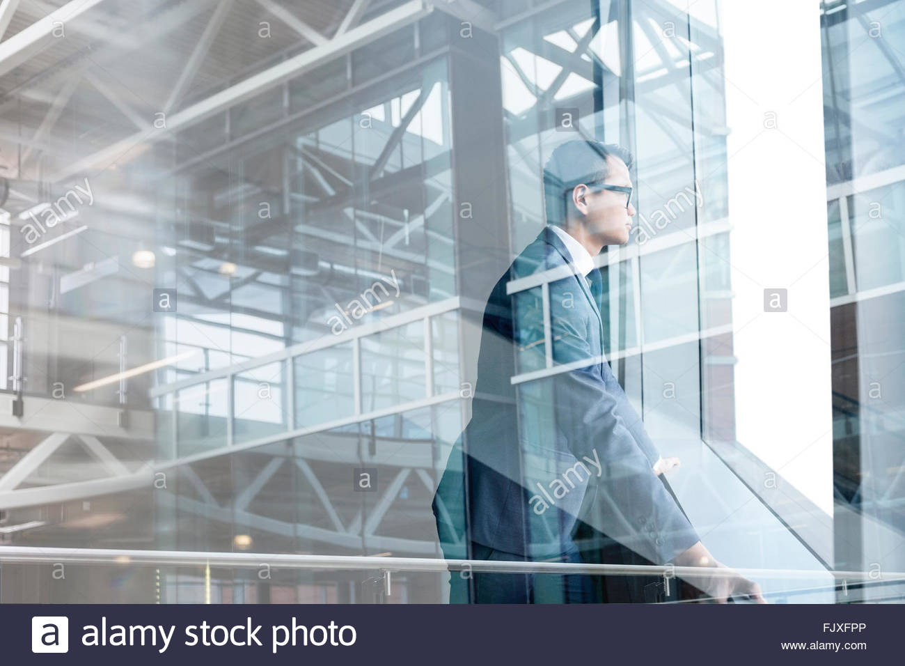 Digital composite businessman looking through modern window - Stock Image