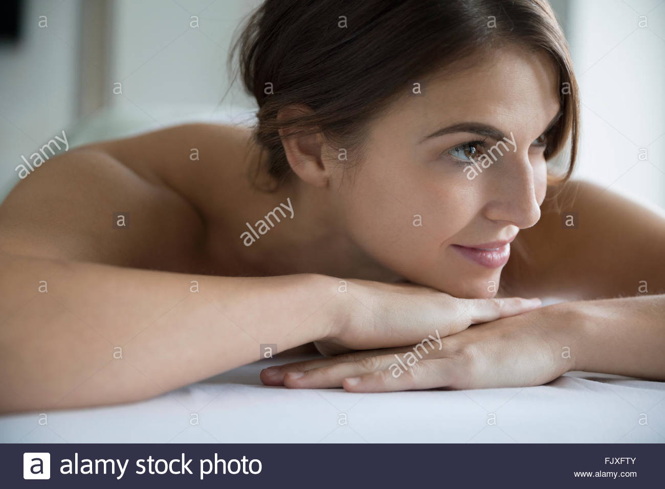 Smiling woman laying on massage table - Stock Image