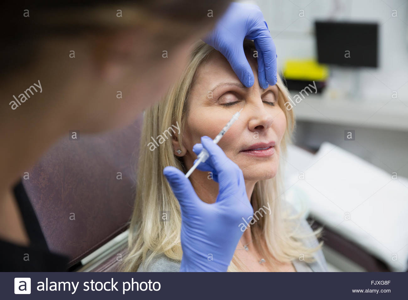 Technician giving woman botox injection side of nose - Stock Image