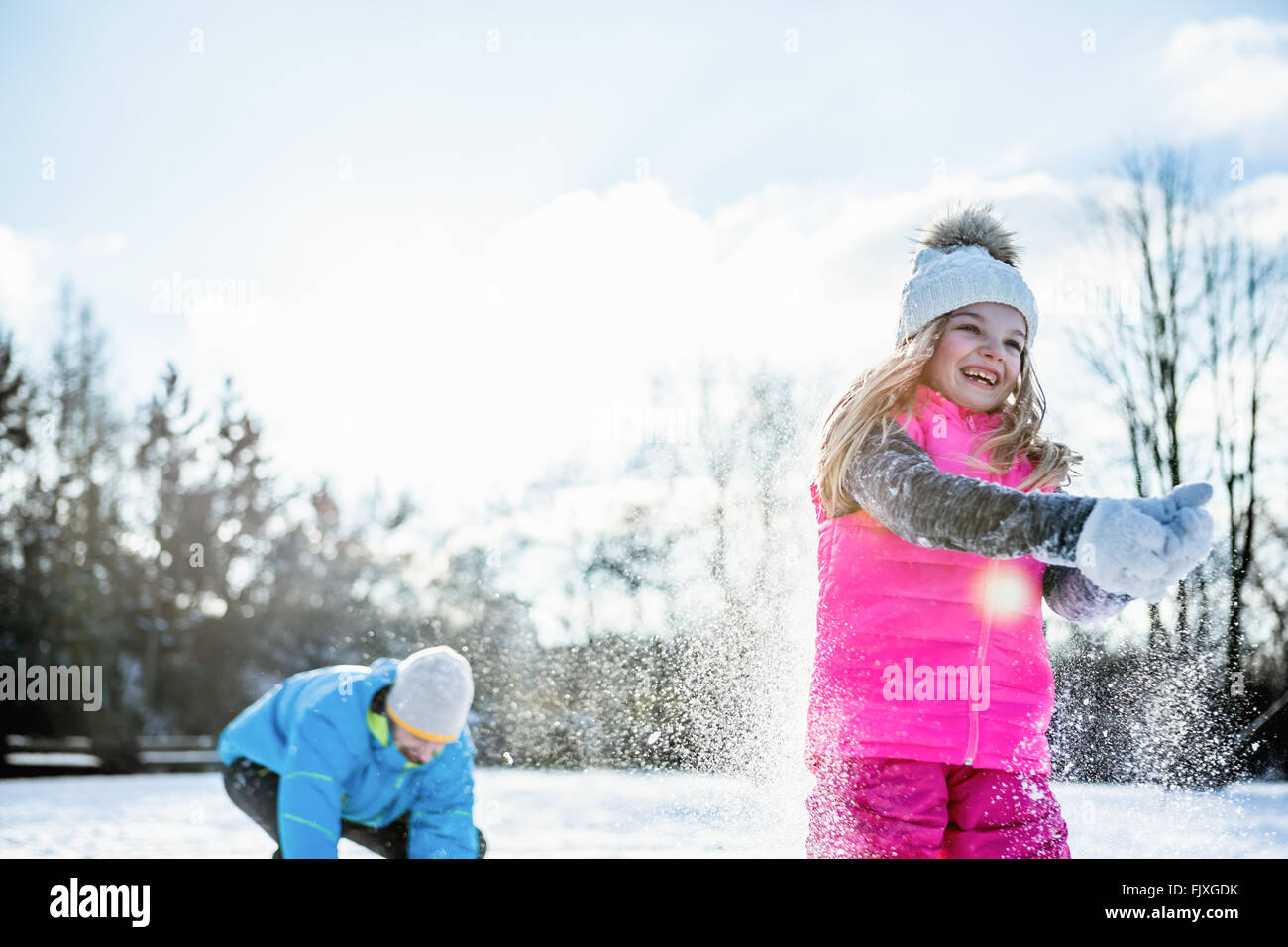Father and daughter playing snowball fight - Stock Image
