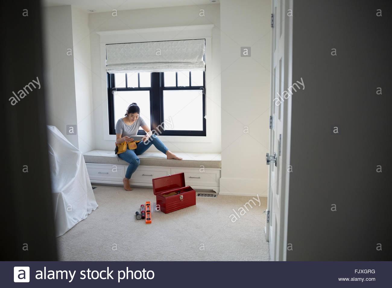 Woman researching DIY on digital tablet in bedroom - Stock Image