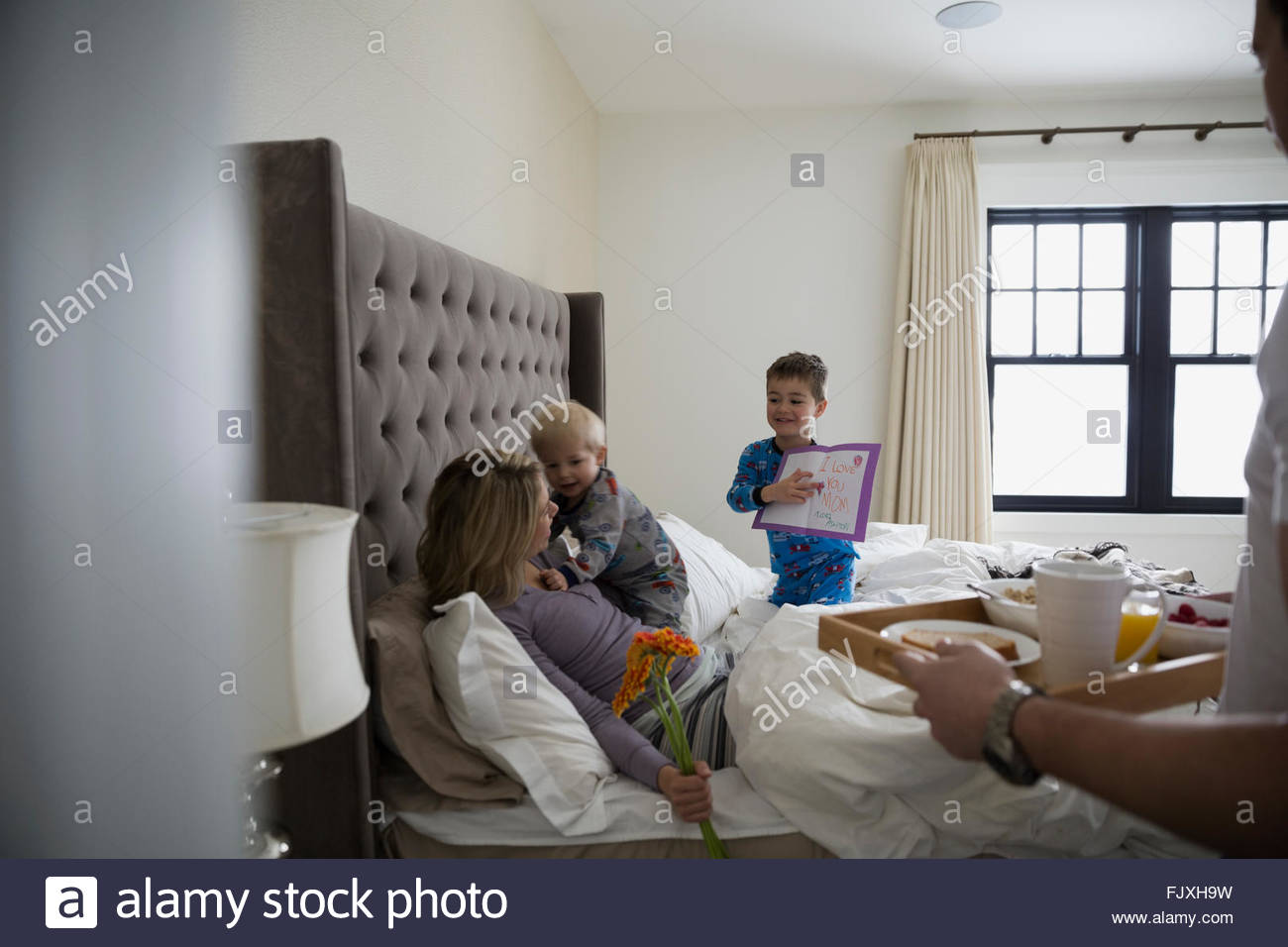 mother receiving breakfast bed mothers day 2-3 - Stock Image