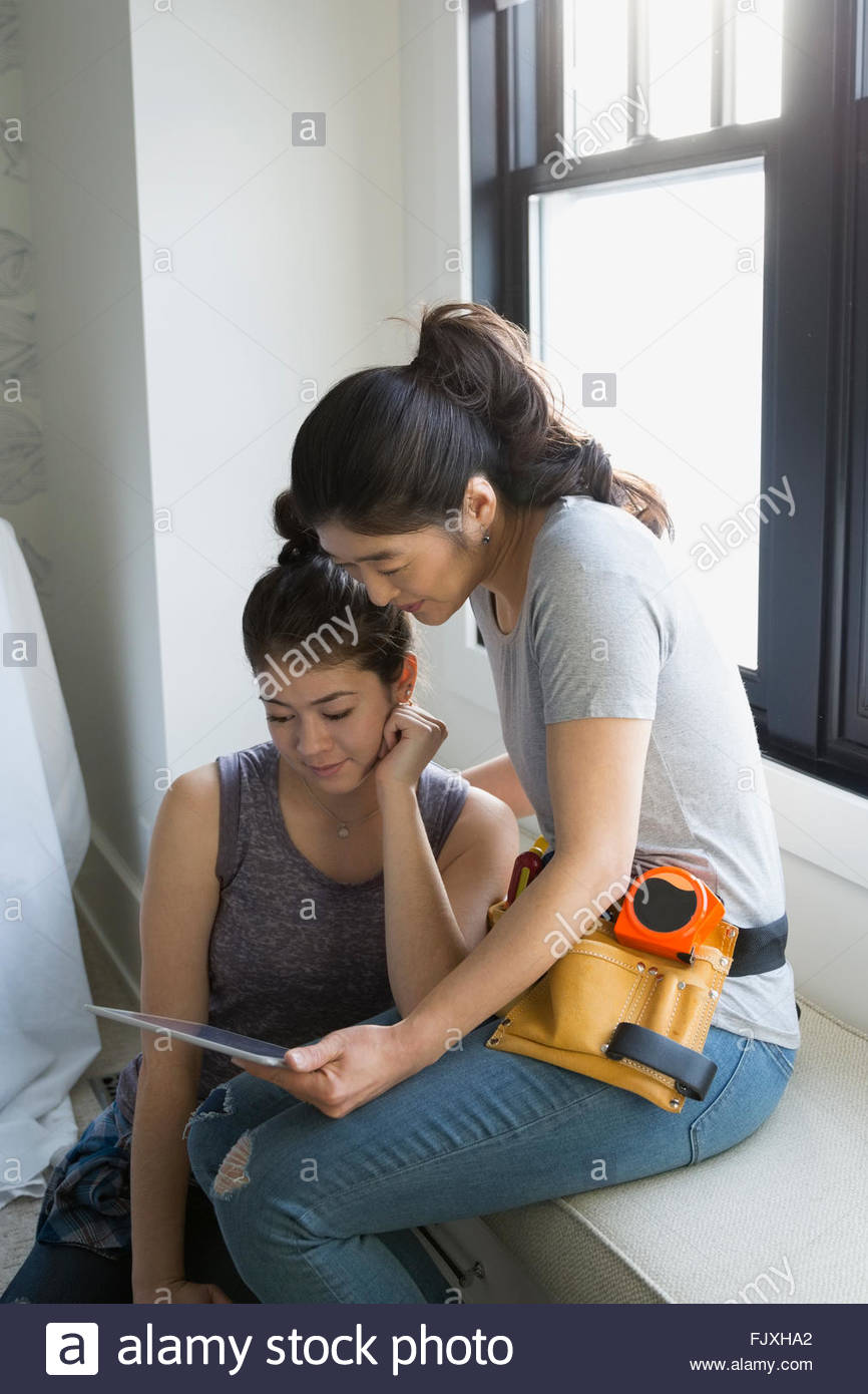 Mother and teenage daughter researching DIY digital tablet - Stock Image