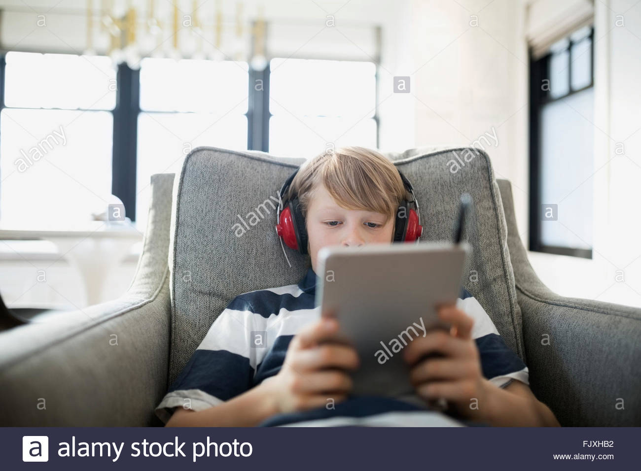 Boy with headphones using digital tablet in armchair - Stock Image