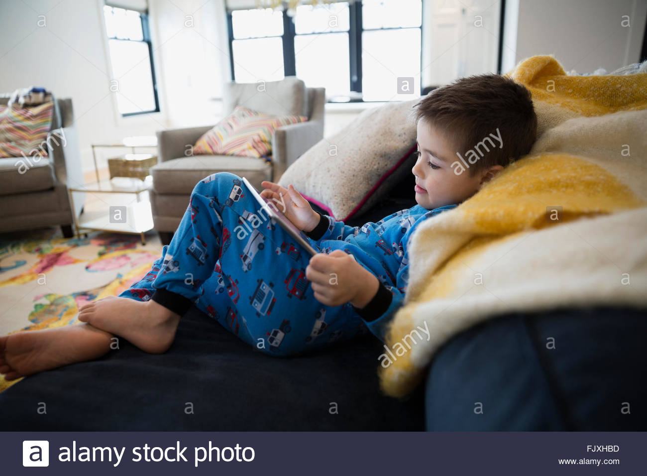 Boy in pajamas using digital tablet on sofa - Stock Image