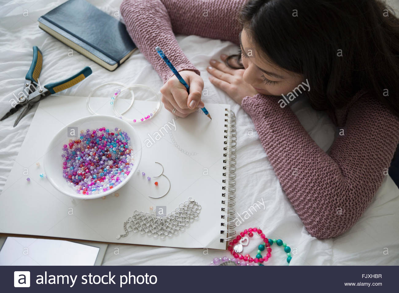 Teenage girl sketching and making jewelry - Stock Image