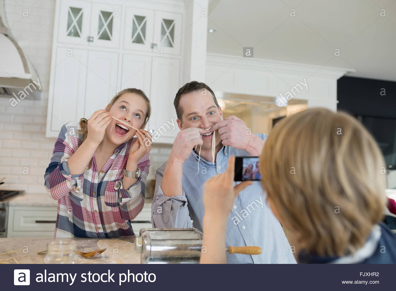 Playful family with long noodle mustaches in kitchen - Stock Image