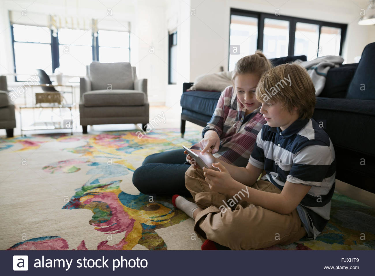 Brother and sister using digital tablet living room - Stock Image