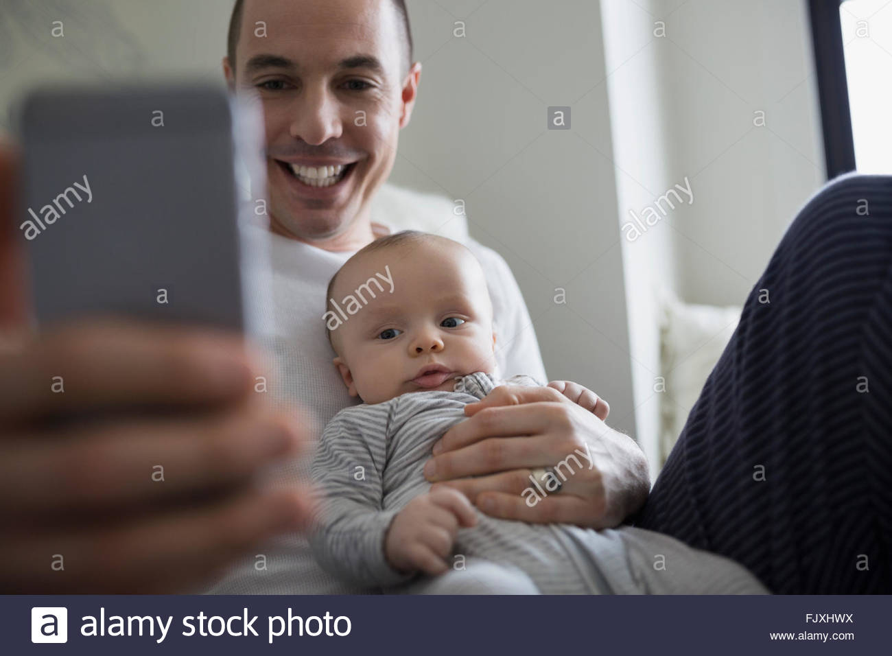 Smiling father and baby son taking selfie - Stock Image