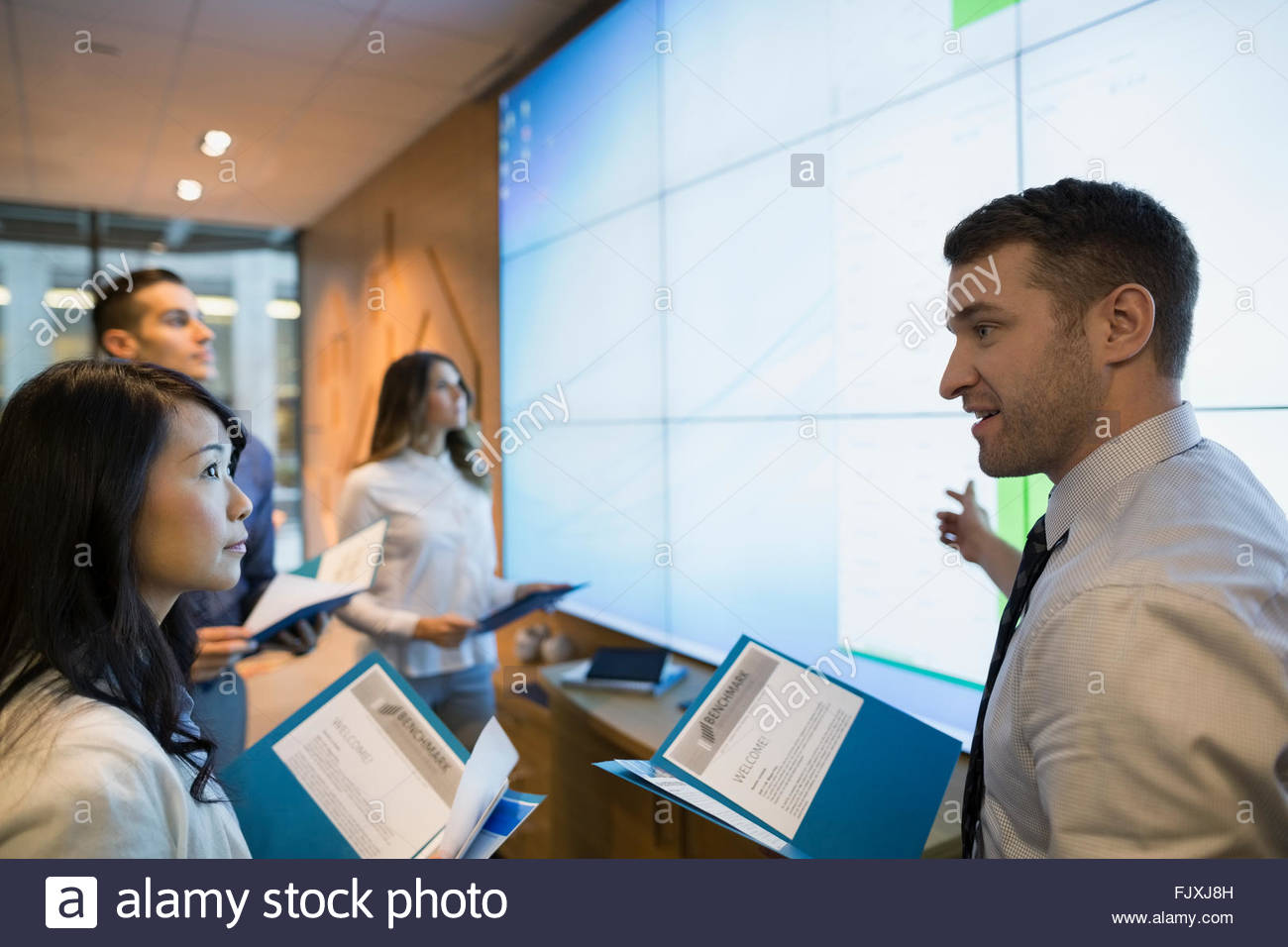 Business people meeting at projection screen conference room - Stock Image