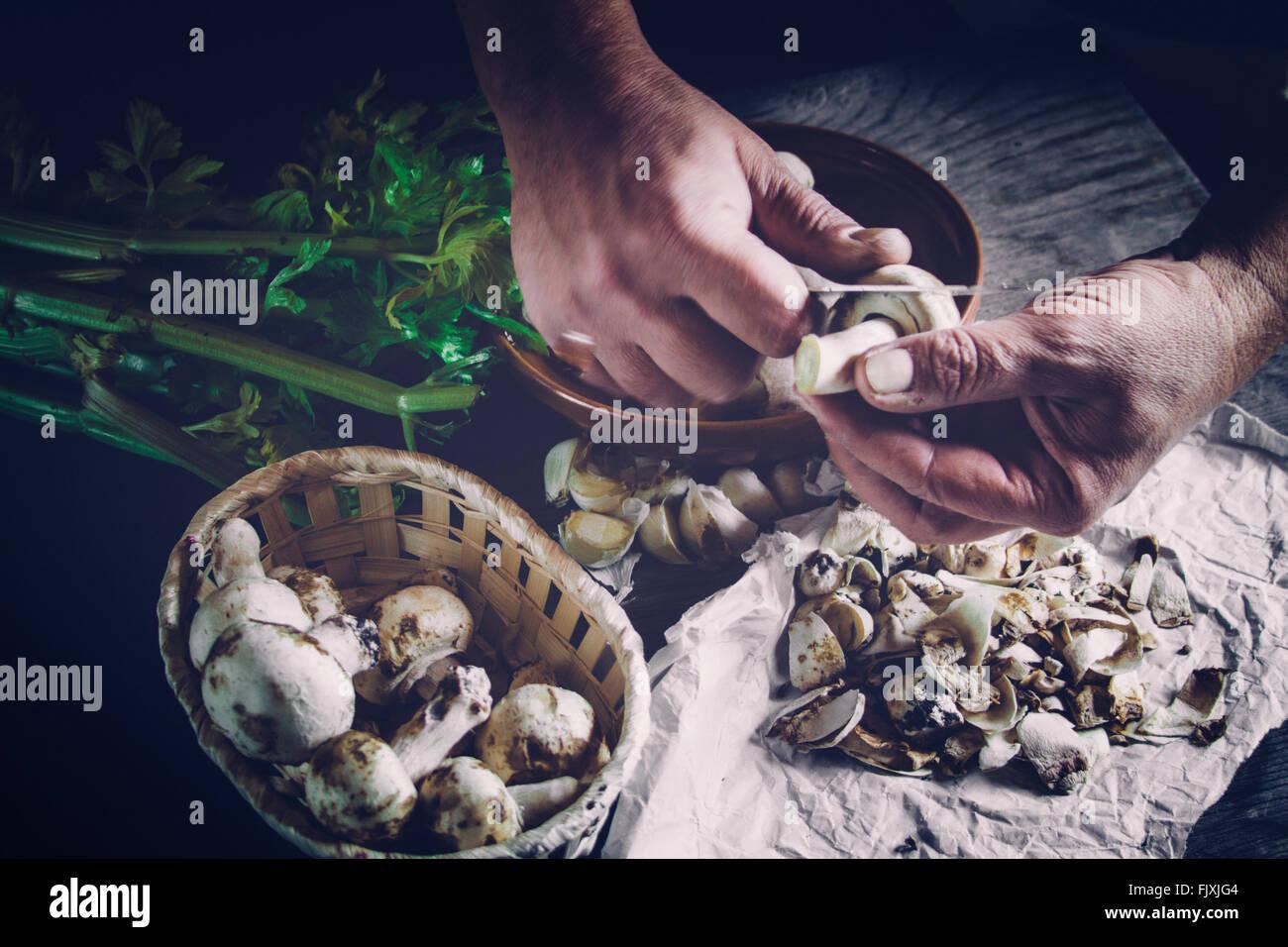 Cropped Image Of Chef Peeling Mushroom On Table Stock Photo