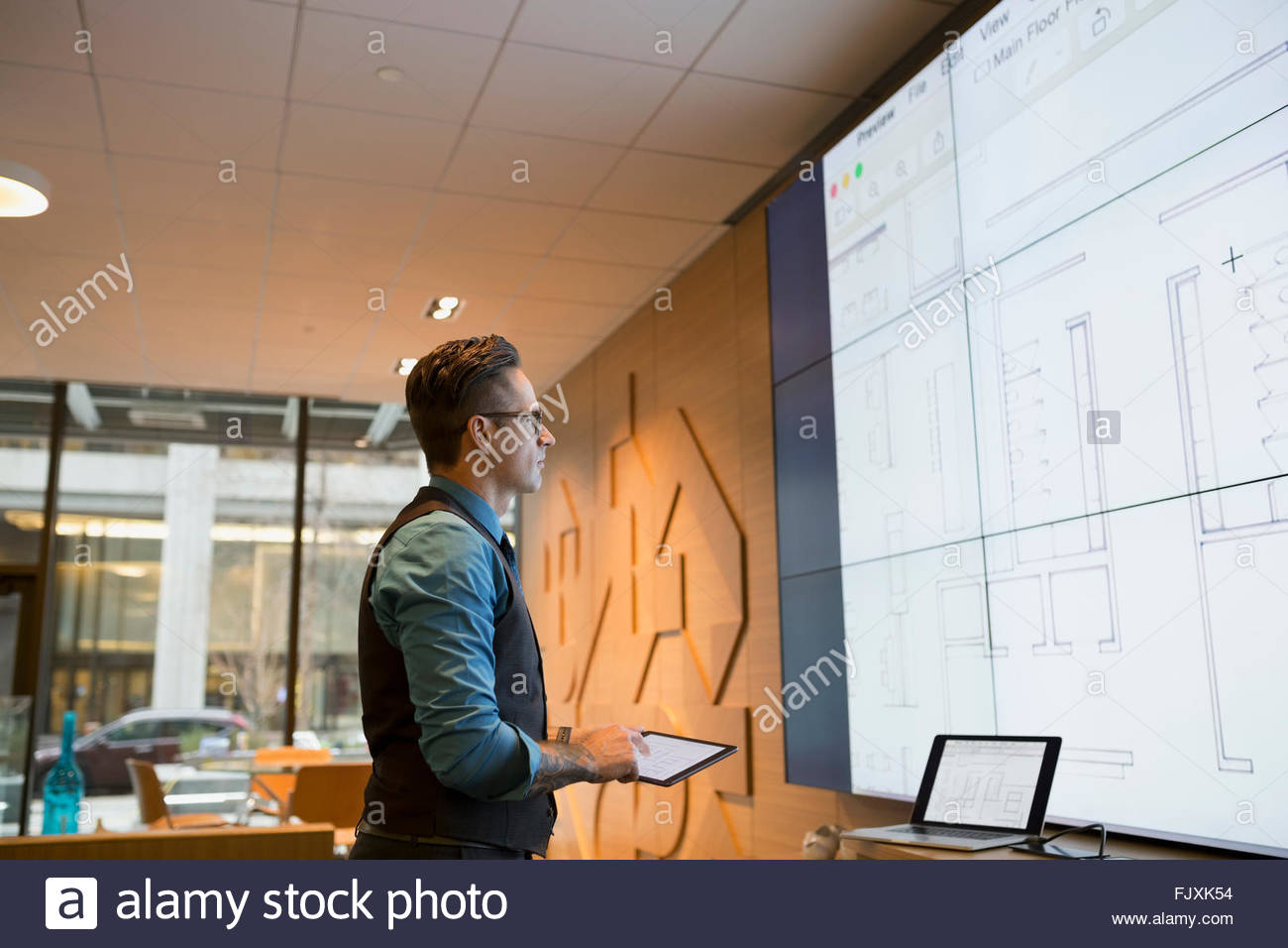 Architect preparing audio visual presentation in conference room - Stock Image