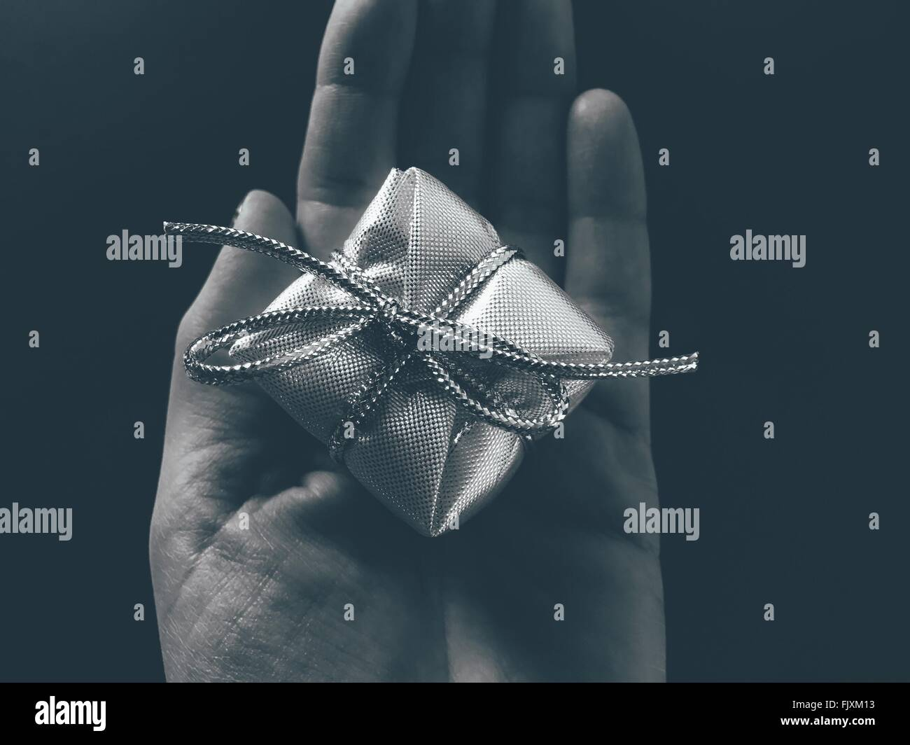 Close-Up Of Hand Holding Gift Over Black Background - Stock Image