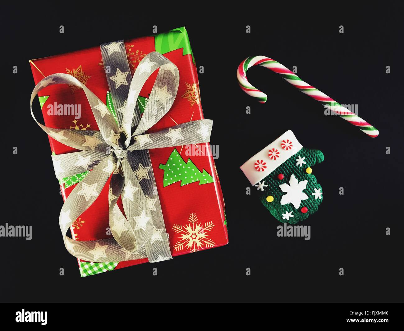 Directly Above Shot Of Gift With Glove Against Black Background - Stock Image