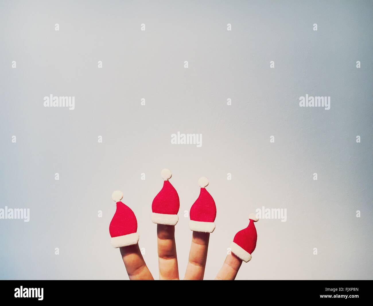 Cropped Image Of Hand With Santa Hats Against White Wall - Stock Image