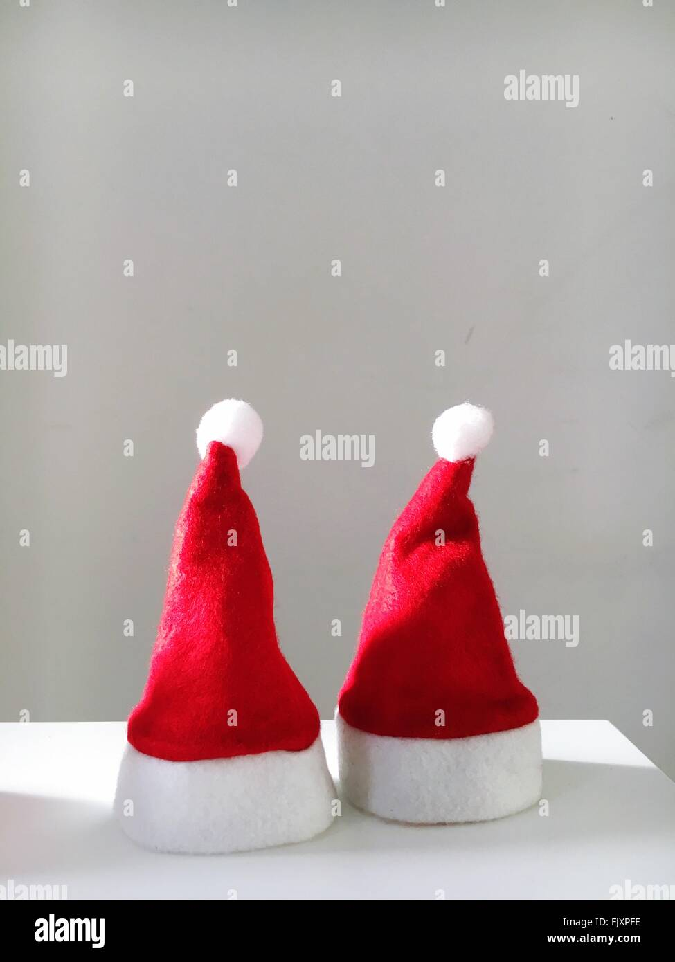 Santa Hats On Table Against Wall - Stock Image