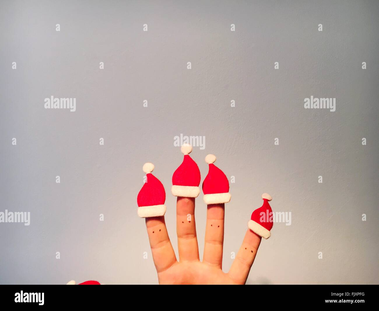 Cropped Hand With Santa Hats Against Wall - Stock Image