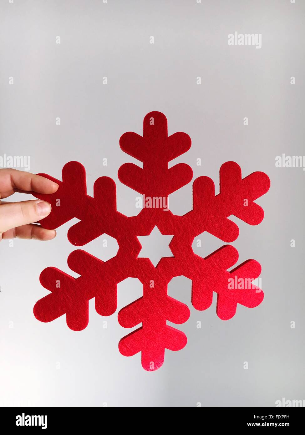 Cropped Hand With Christmas Decoration Against Wall - Stock Image