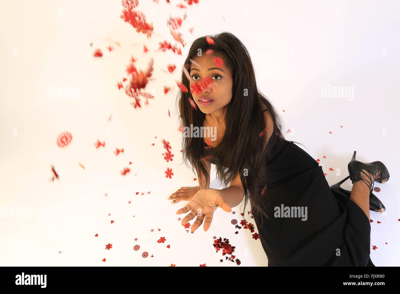 High Angle View Of Fashion Model Throwing Artificial Leaves Over White Background - Stock Image