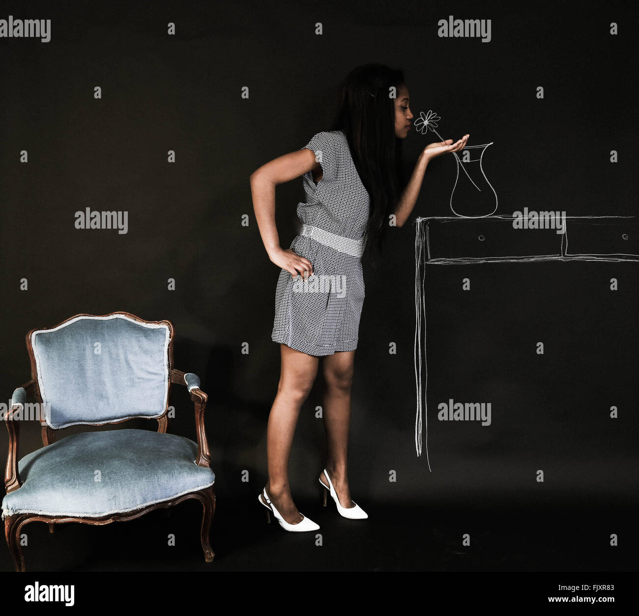 Optical Illusion Of Woman Smelling Flower Drawing On Wall - Stock Image