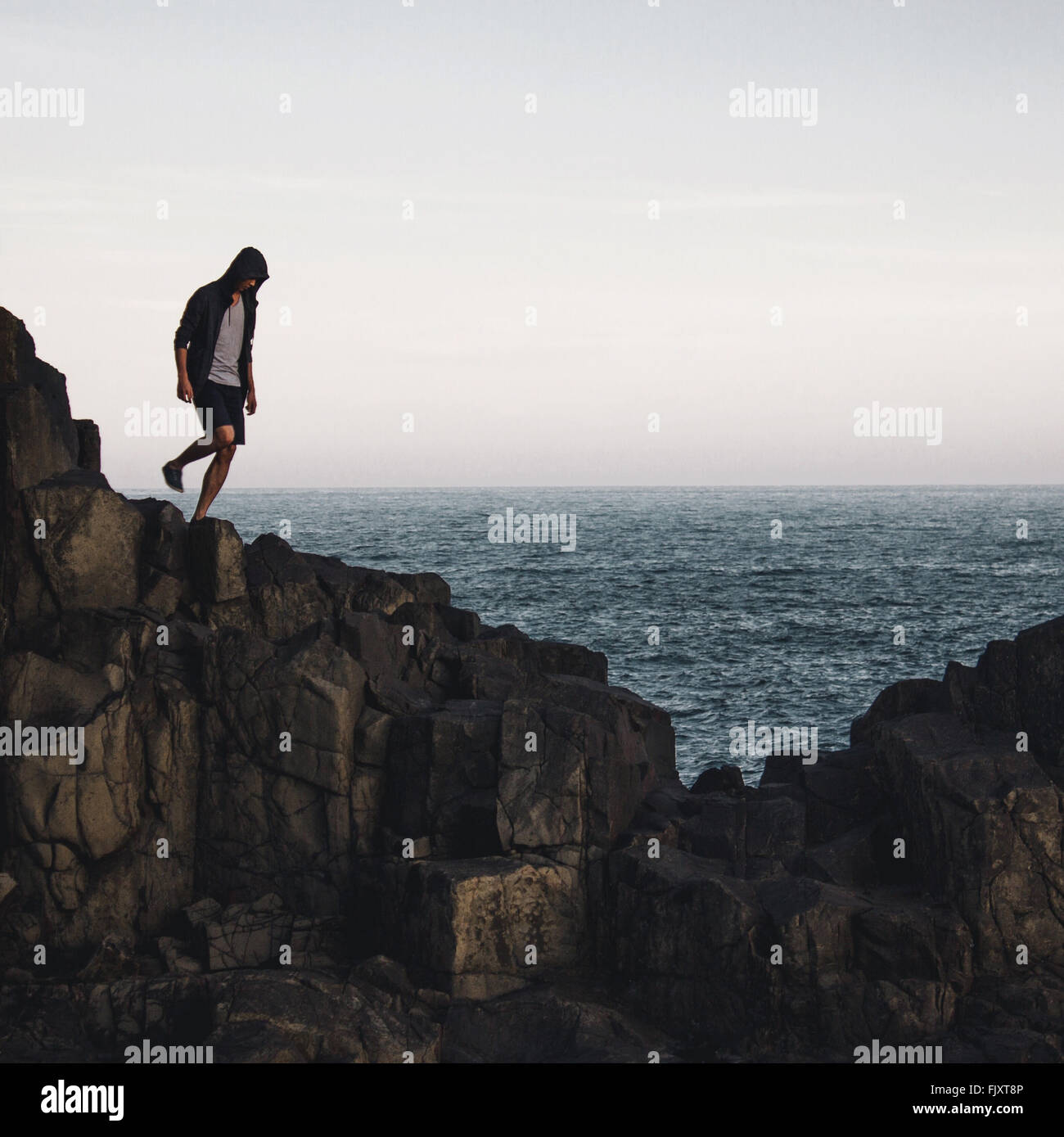Man Standing On Cliff By Sea Against Sky - Stock Image