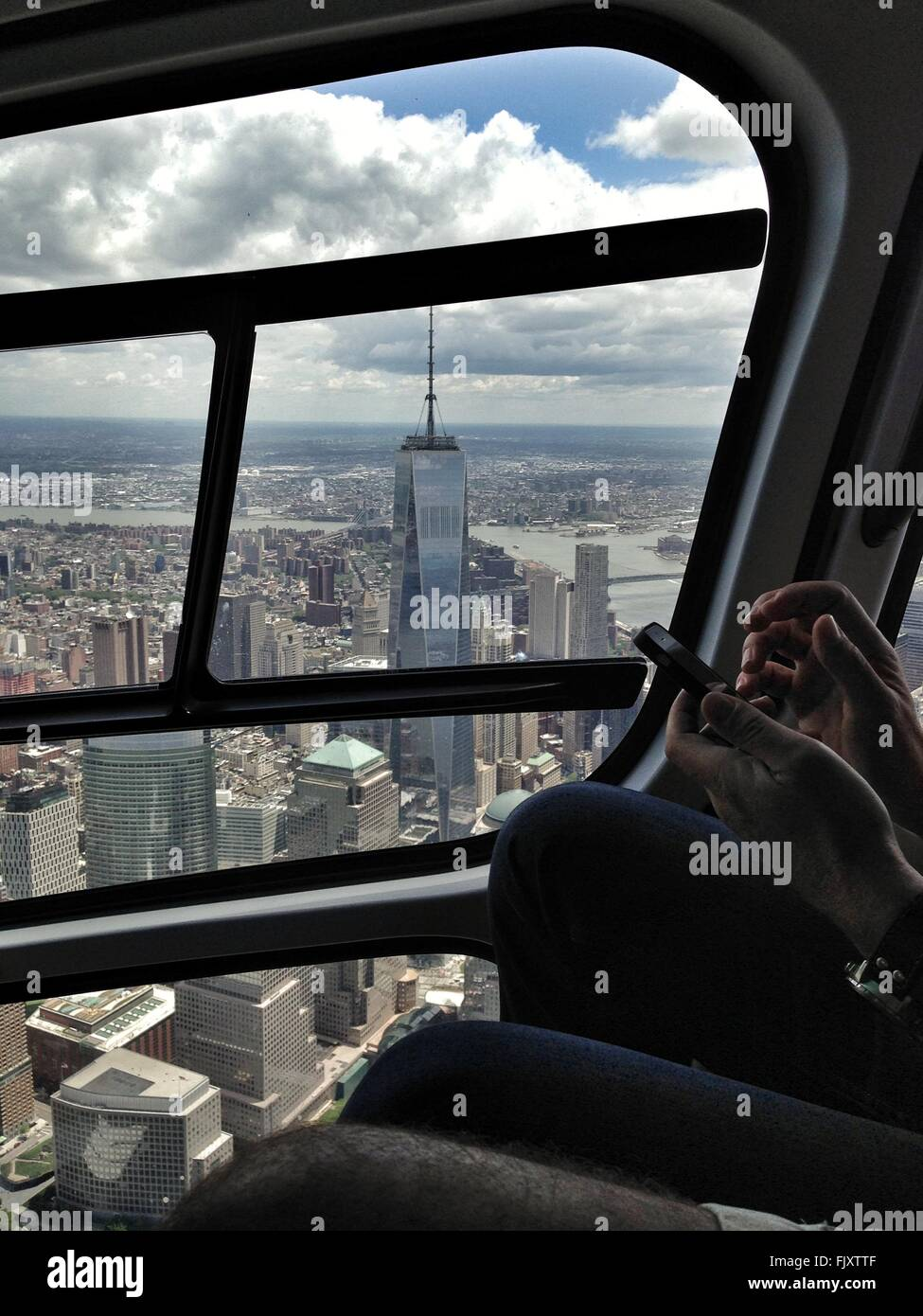 Cropped Hands Of Man Using Mobile Phone In Helicopter - Stock Image
