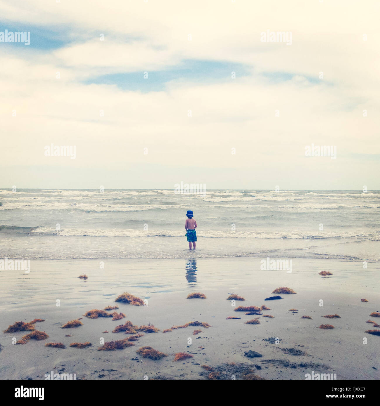 Rear View Of Shirtless Boy Standing At Sea Shore Against Cloudy Sky - Stock Image