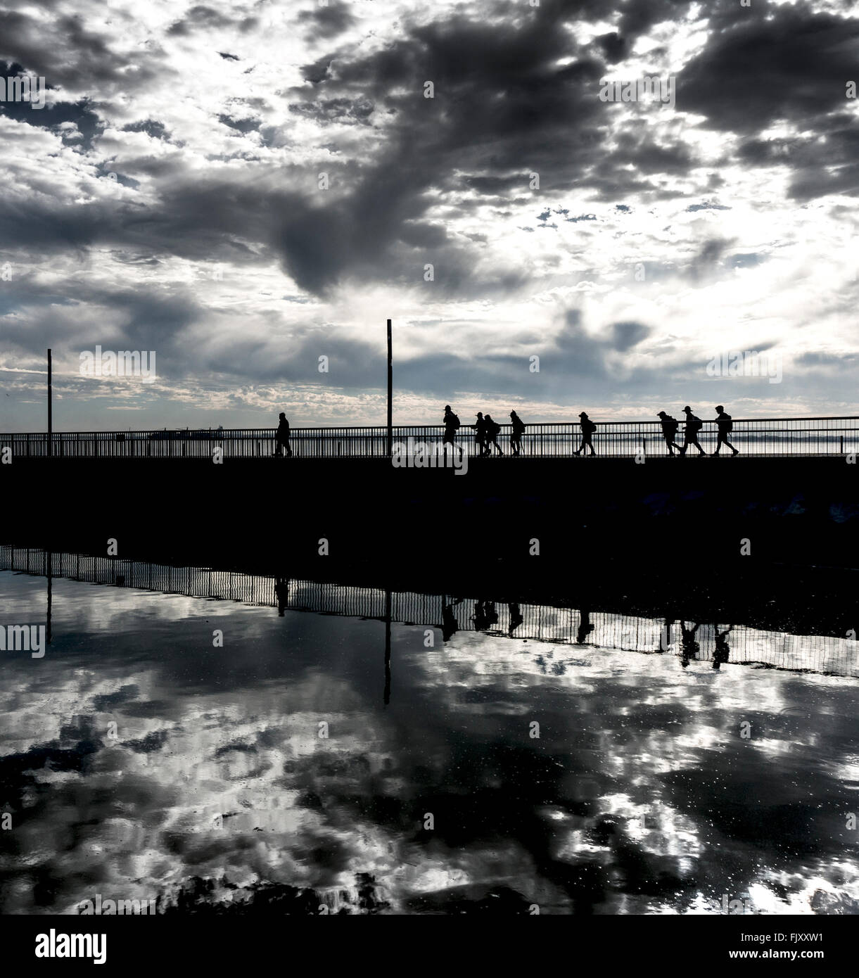 People Walking On Silhouette Bridge Over Calm River Against Cloudy Sky Stock Photo