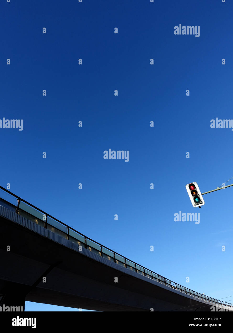 Low Angle View Of Signal And Elevated Road Against Clear Blue Sky - Stock Image