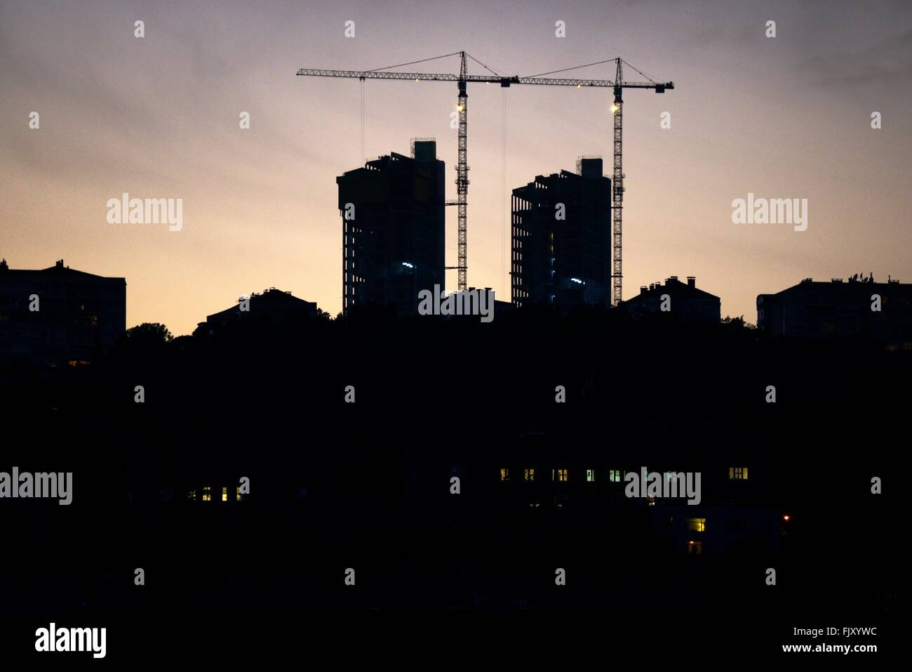 Apartment office blocks under construction rise above the Bosphorus near the Rumelihisari Castle. Sariyer, Istanbul, - Stock Image