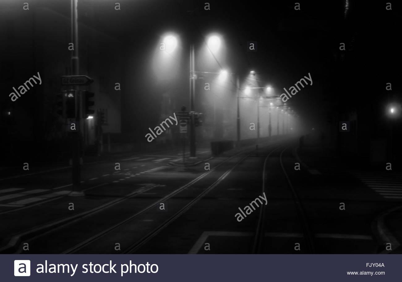 Railroad Tracks On Street At Night - Stock Image