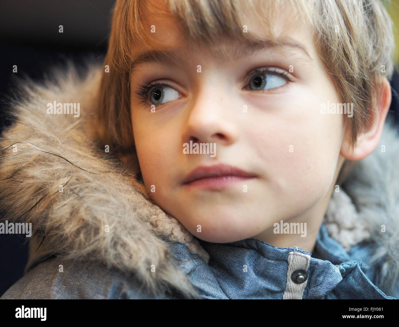 Close-Up Of Boy Wearing Fur Jacket In Car - Stock Image