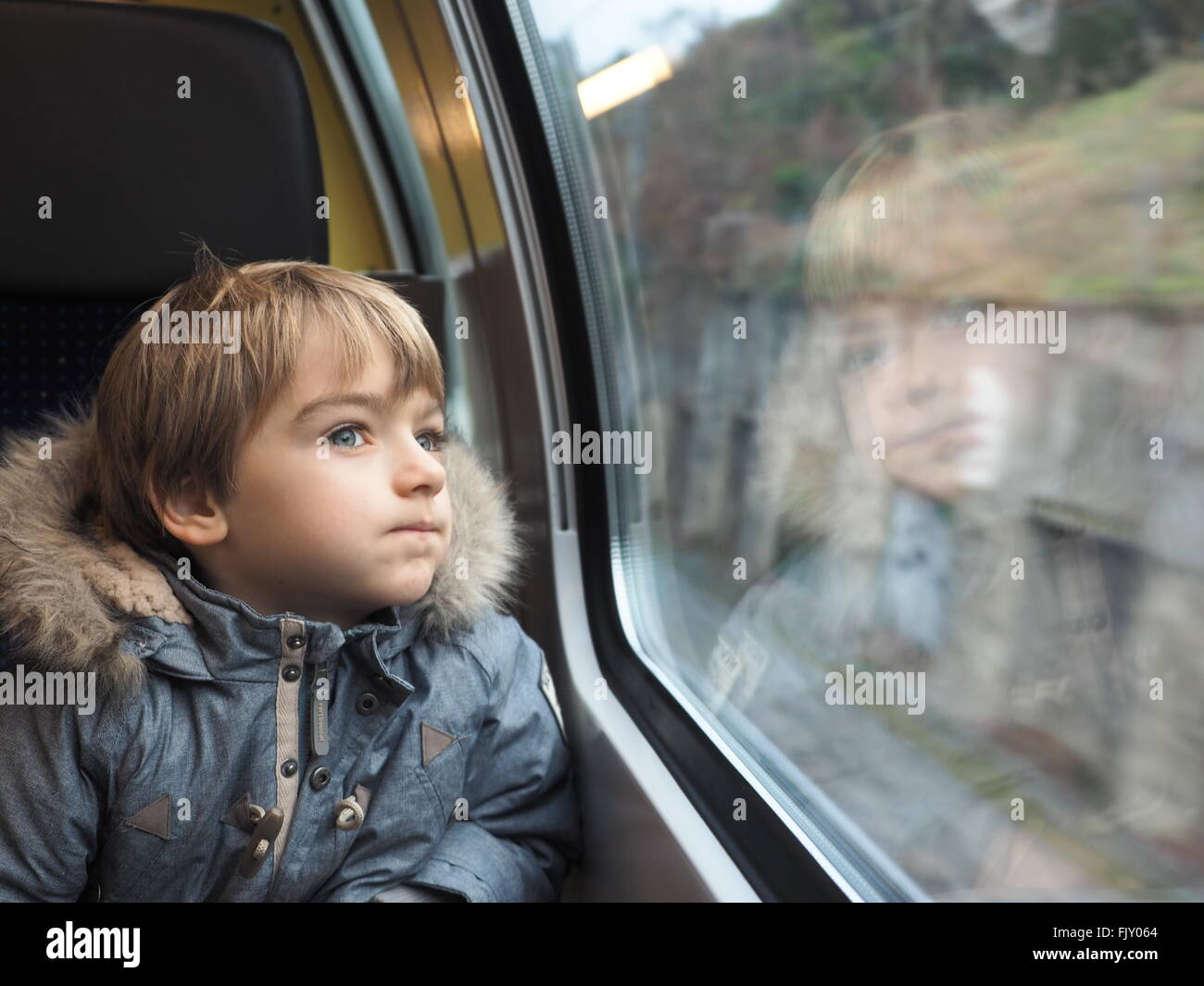 Close-Up Of Boy Wearing Fur Jacket Looking Through Car Window - Stock Image