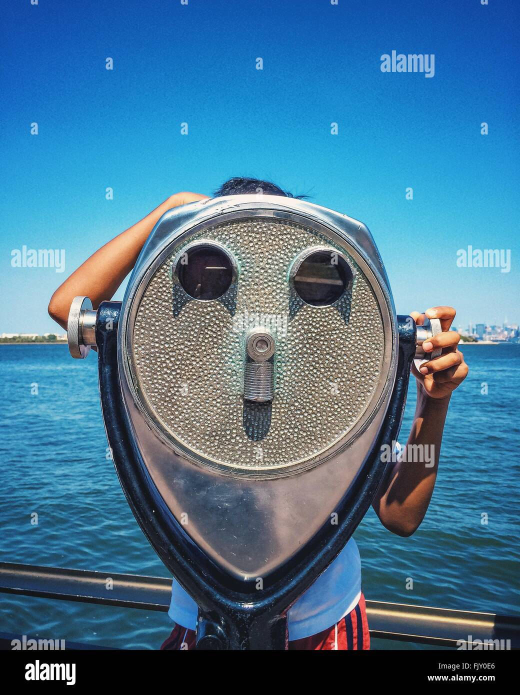 Person Looking Through Coin-Operated Binoculars By Sea At Liberty Island - Stock Image
