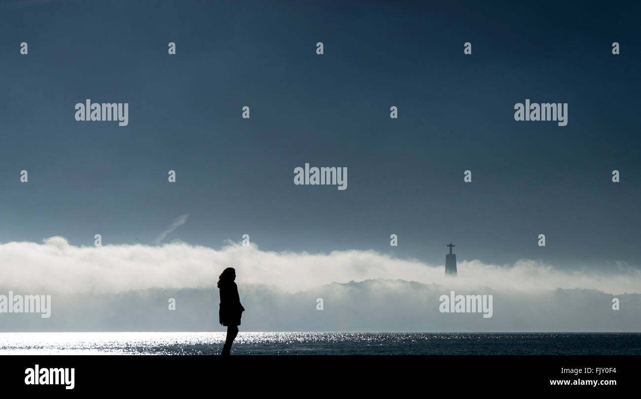 Silhouette Woman Standing By Sea Against Sky - Stock Image