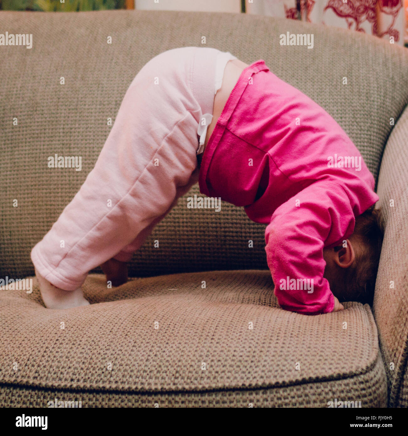 Side View Of Baby Girls Doing Headstand On Sofa At Home Stock Photo