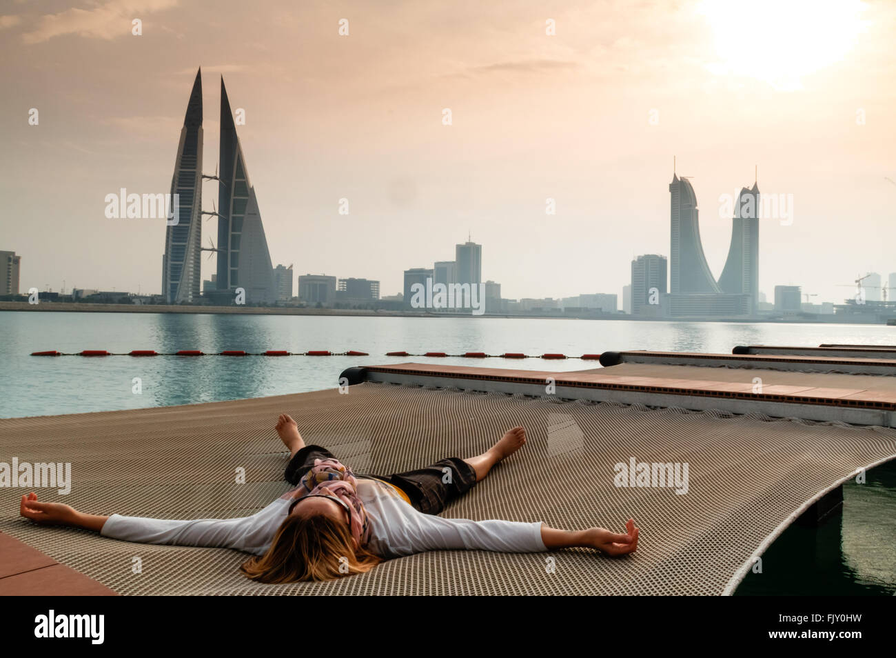 Woman Lying On Net At Pier Against Sky - Stock Image