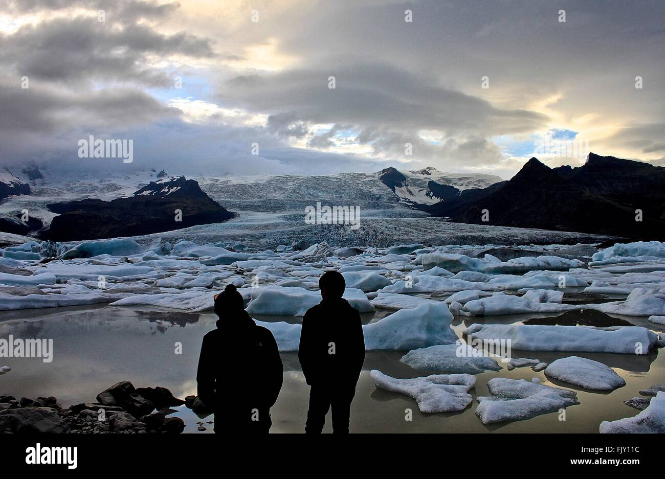 Rear View Of Silhouette Men Standing In Front Of Glaciers At Sunset - Stock Image
