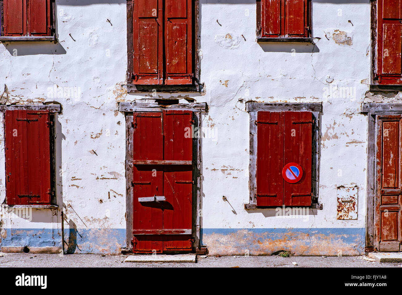 Red Doors And Windows On Building On Sunny Day - Stock Image