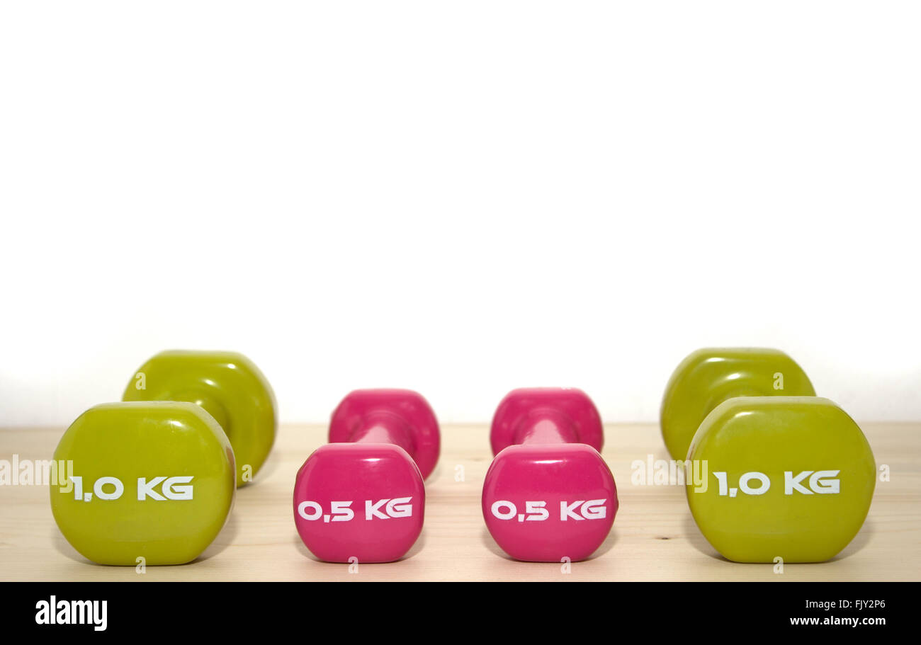 Four weights on white and wooden background - Stock Image