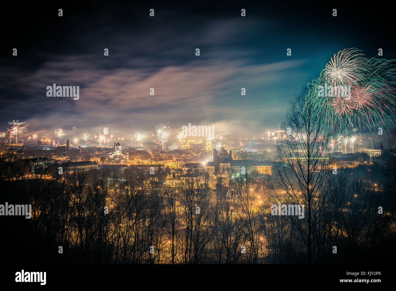 Firework Exploding Over Illuminated City Against Sky - Stock Image