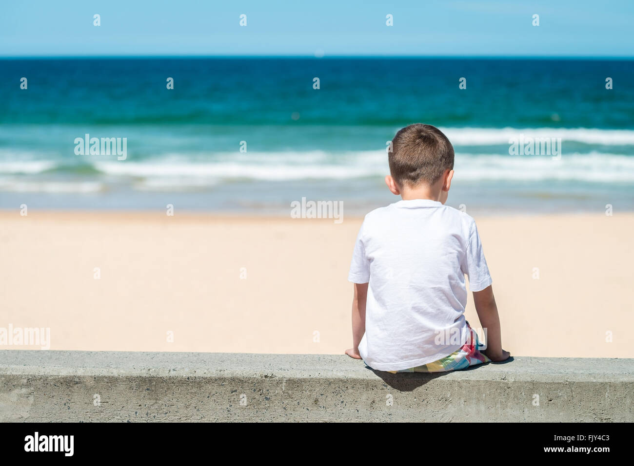 Sad boy sitting at he beach and thinking about something stock image