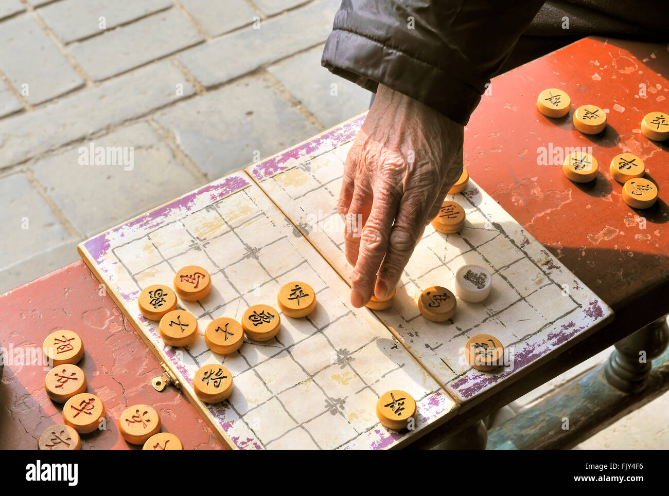 A man makes a move on a on a local Beijing Chinese chess game board. Xiangqi, also known as Chinese chess, is an - Stock Image