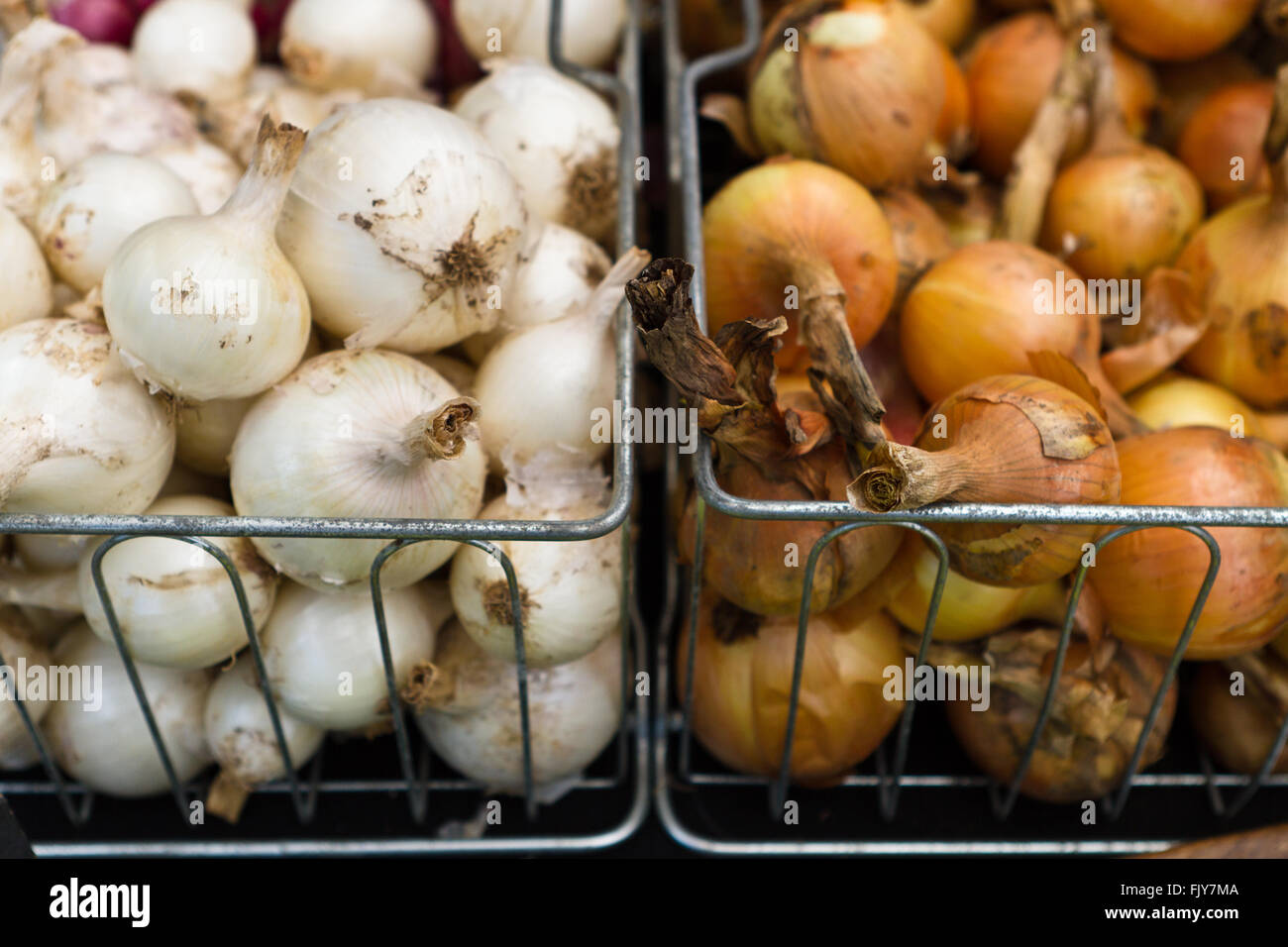 Freshly picked onions in baskets at outdoor farmers market Stock Photo