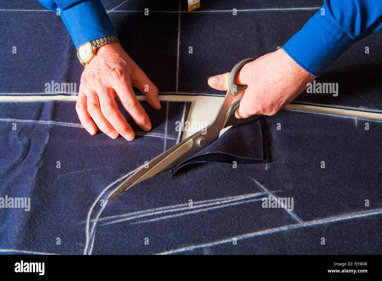 Tailor Cutting Fabric to a New Coat with Scissors. - Stock Image