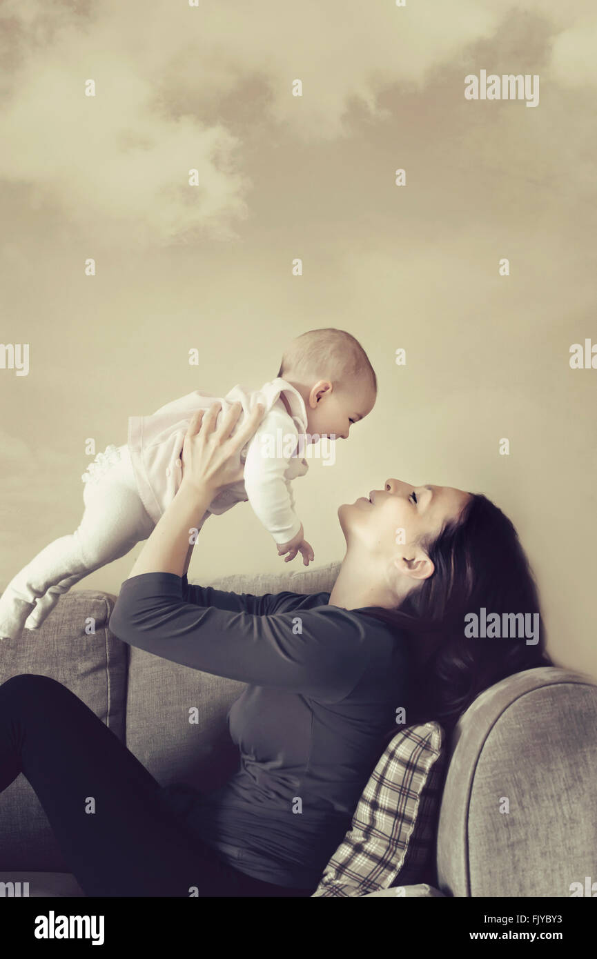young mother playing with her baby girl on the sofa bed - Stock Image