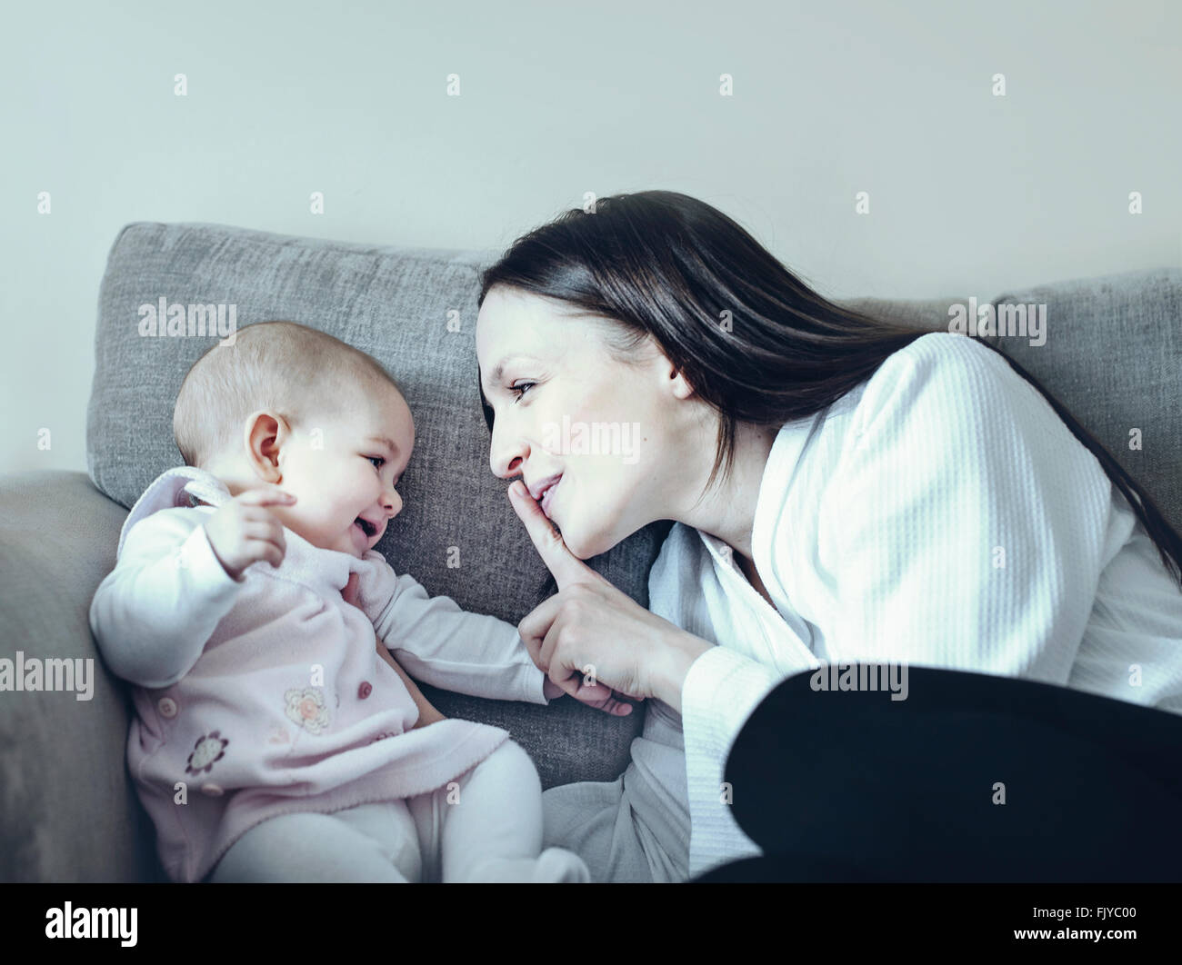 young woman playing with her baby girl on the sofa bed - Stock Image