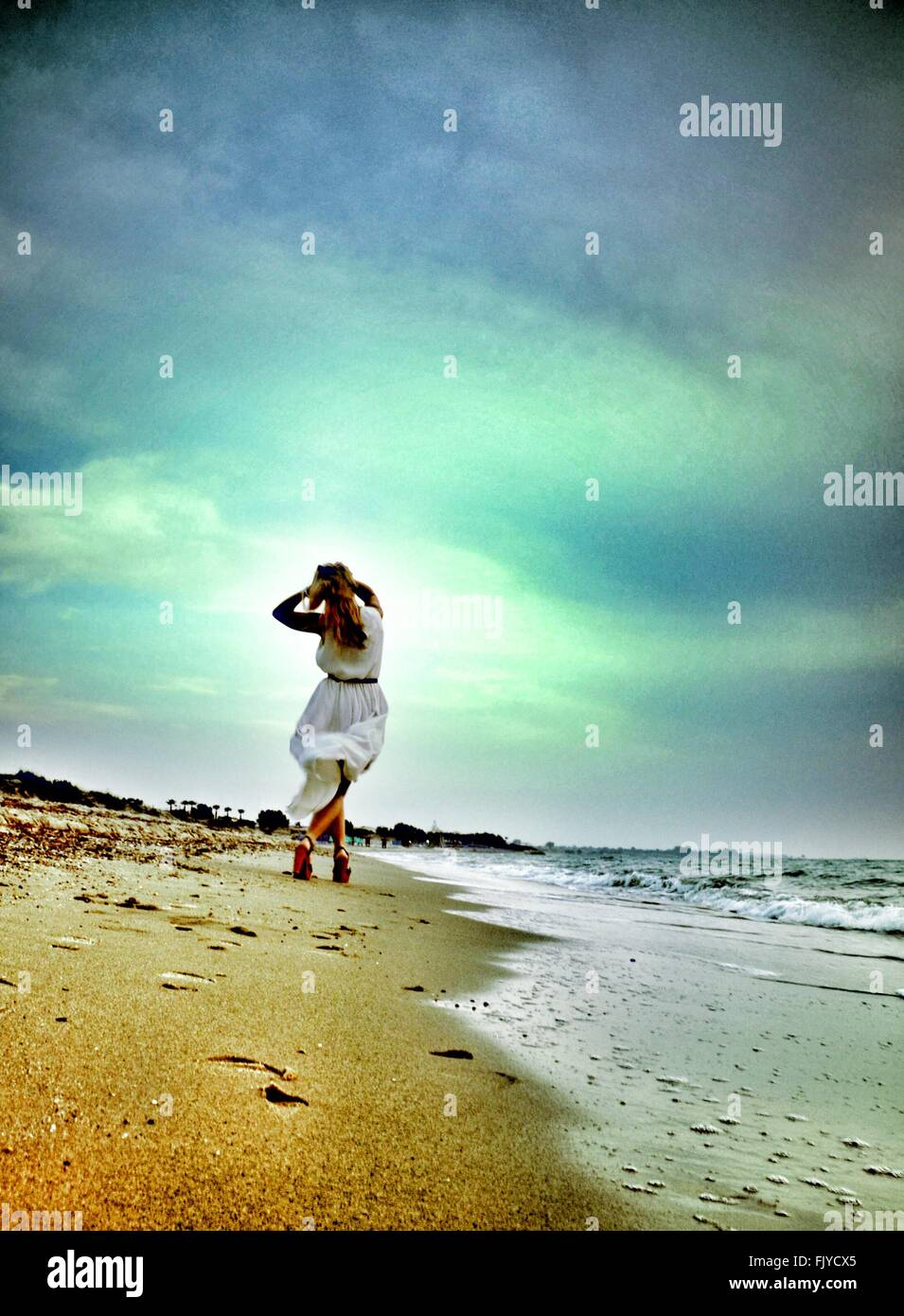 Low Angle View Of Young Woman Walking On Beach Against Cloudy Sky - Stock Image