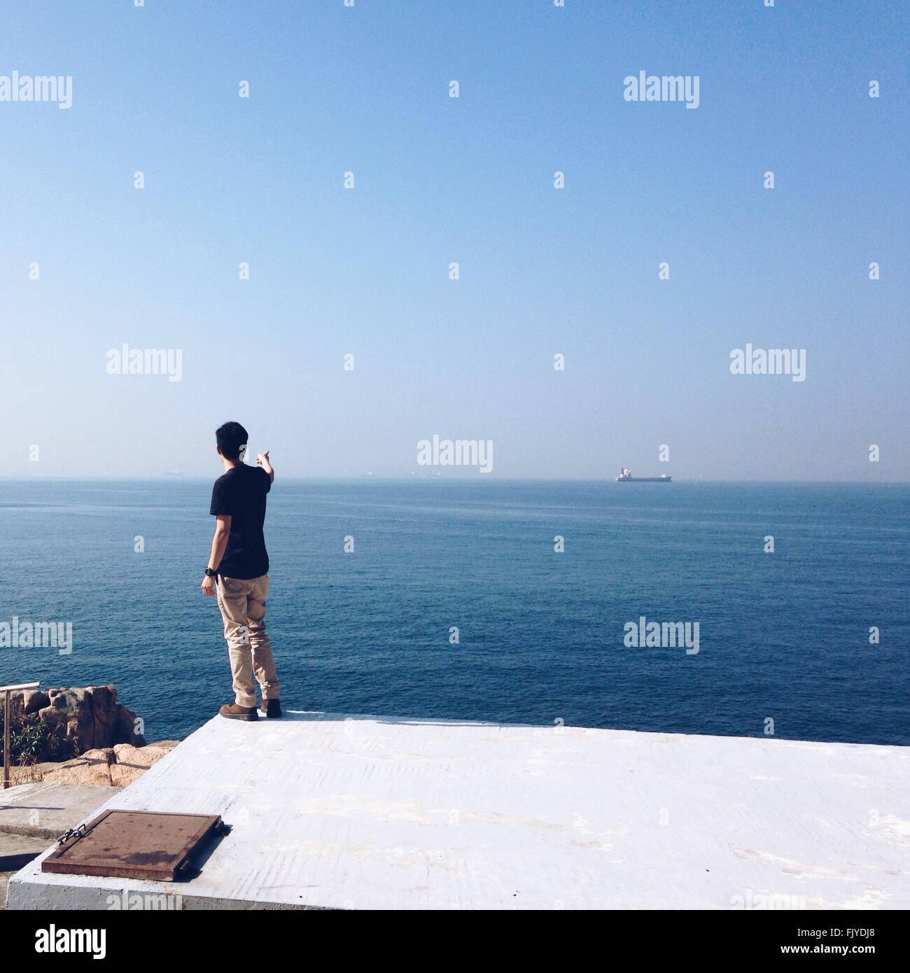 Fill Length Of Man Pointing Towards Ship In Sea Against Clear Blue Sky - Stock Image